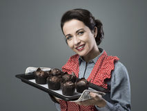 Vintage housewife with home made muffins. Smiling vintage woman holding a baking tray with chocolate home made muffins Royalty Free Stock Photos