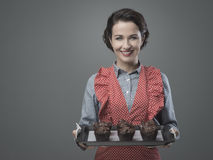 Vintage housewife with home made muffins. Smiling vintage woman holding a baking tray with chocolate home made muffins Royalty Free Stock Image