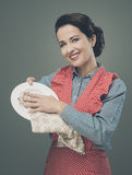VIntage housewife polishing dishware. Smiling vintage housewife drying and polishing a dish with a cloth Royalty Free Stock Image