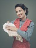 VIntage housewife polishing dishware Royalty Free Stock Image
