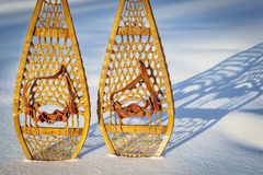 Vintage Huron snowshoes abstract. Vintage wooden Huron snowshoes with leather binding in snow with shadow Stock Images