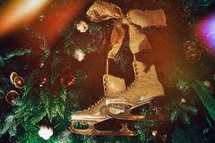 Vintage ice skates hanging on Christmas tree. Vintage old white ice skates hanging on decorated Christmas trees as toys Royalty Free Stock Photo