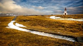 Vintage Icelandic church stands in middle of meadow of high gras royalty free stock photos