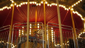 Vintage illuminated carousel spinning at night in amusement park. Vintage carousel spinning at night in amusement park stock video