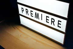 Vintage illuminated Premiere sign in cinema movie. Vintage illuminated lightbox Premiere sign in cinema movie or for radio and television live audience broadcast Stock Photo
