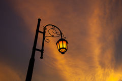 Vintage illuminated street lamps orange light with sunset cloud Royalty Free Stock Photos