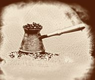Vintage image background with old-style cezve. With coffee beans on sackcloth Royalty Free Stock Photo