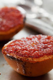 Vintage image of broiled grapefruit with brown sugar and cinnamon on metal surface, healthy dessert is good for breakfast. Or snacks stock image