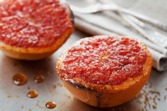 Vintage image of broiled grapefruit with brown sugar and cinnamon on metal surface, healthy dessert is good for breakfast. Or snacks royalty free stock photo