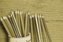 Vintage image of drawing pencils and wood wall. Vintage image of drawing pencils in ceramic pot on wooden wall background Stock Photos