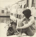 Girl sitting on the side of a bridge in Venice watching a gondola pass, in the 60s royalty free stock image