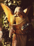 Vintage image of a sad angel on a cemetery against the backgroun Royalty Free Stock Photo