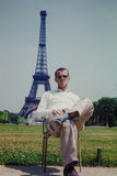 Vintage image of a tourist sitting in front of the Eiffel Tower, Paris, France. Royalty Free Stock Photography