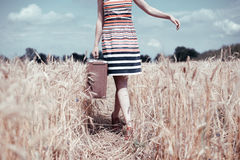 Vintage image of young woman walking on field with Stock Photos