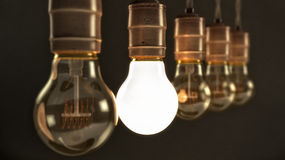 Vintage Incandescent Light Bulbs with one Illuminated. Five hanging vintage incandescent light bulbs over dark background with one illuminated Stock Photos