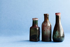 Vintage ink bottles on blue paper background. Aged dirty glass accessories. copy space, horizontal photo.  stock image