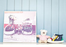 Vintage inspiring poster and baby shoes. Vintage inspiring poster with old bicycle - flowerbed, teddy bear toy and cute tiny baby shoes on the bookshelf on blue Royalty Free Stock Photos
