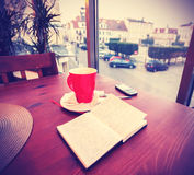Vintage instagram like toned coffee cup and diary in coffee shop Stock Photo