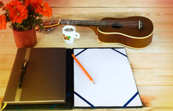 (Vintage and instagram look) blank A4 note and pencil on wooden. Table with background of ukulele and cup of coffee Stock Photos
