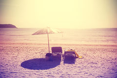 Vintage instagram stylized beach chairs and umbrella at sunset. Royalty Free Stock Photo