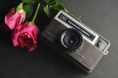 Vintage instamatic Camera. Old vintage instamatic camera with pink roses Stock Photo
