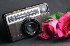 Vintage instamatic Camera. Old vintage instamatic camera with pink roses Stock Photography