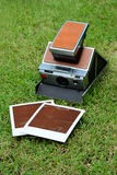 Vintage instant camera with empty prints. On green grass Stock Image