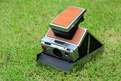 Vintage instant camera on green grass. The vintage instant camera on green grass Stock Photo