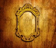 Vintage interior design. Old golden mirror frame on retro grunge wall, artwork and picture aged framework, abstract dark background, wallpaper floral pattern Stock Photos
