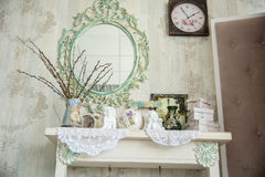 Vintage interior with mirror and a table with a vase and willows. Designer wall clock. Angels on the table royalty free stock photos