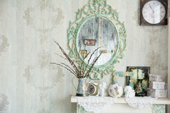 Vintage interior with mirror and a table with a vase and willows. Designer wall clock. Angels on the table royalty free stock image