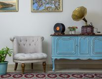 Retro off white armchair, vintage wooden light blue sideboard, old phonograph gramophone and vinyl records Royalty Free Stock Photo