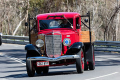 Vintage International Flat bed truck driving on country road. Adelaide, Australia - September 25, 2016: Vintage International Flat bed truck driving on country Royalty Free Stock Photography