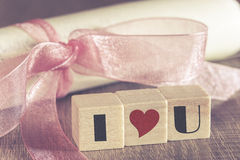 Vintage invitation with pink ribbon and I Love You message Stock Images
