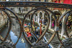 Vintage iron railing on a bridge in Venice. View from the bridge on the Venetian canal with gondolas and people Stock Images