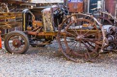Vintage Iron Tractor In Salvage Yard. Vintage Rusty Tractor With Large Iron Wheels In Salvage Yard Stock Photo