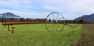 Vintage Irrigation System on Agricultural Land. Vintage looking commercial farm irrigation line system on wheels on a green field that runs parallel to a tilled Stock Image