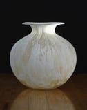 Vintage Italian Glass Vase profile. Vintage Italian glass vase in medium profile on wooden floor against black background. Round with pronounced lip. Light plays Stock Photo