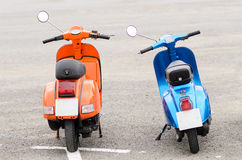 Vintage Italian Motorcycle. Colorful couple of vintage oldtimer scooters, one orange and other blue Stock Image