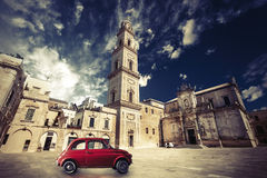 Vintage Italian scene, an old church with a bell tower and old small red car Royalty Free Stock Photos