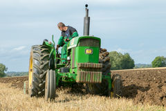 Vintage John Deere tractor pulling a plough. Vintage John Deere tractor ploughing a field with plough working stubble field with farmer Royalty Free Stock Photo