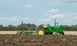Vintage John Deere tractor pulling a plough Royalty Free Stock Photo
