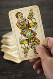 Vintage joker playing card. Hand holding a joker playing card catch from the deck Royalty Free Stock Image