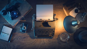 Vintage journalist's desk. Retro journalist's desk 1950s style with vintage typewriter, phone and lamp at night time, top view Royalty Free Stock Image