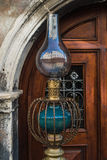 Vintage kerosene lamp . Old austran doors on background Royalty Free Stock Images