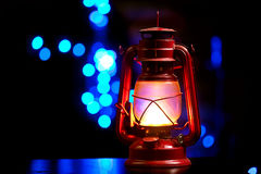 Vintage kerosene oil lantern. Lamp burning with a soft glow light in an antique rustic country barn with aged wood floor Royalty Free Stock Images