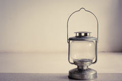 Vintage kerosene oil lantern lamp standing on cement floor with white wall background. Vintage filter effect royalty free stock images