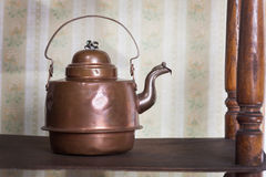 Vintage kettle on old bookshelf in the background retro wallpaper Royalty Free Stock Image