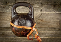 Vintage kettlebell on a wooden background with tape-measure Royalty Free Stock Images