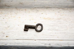 Vintage key at dirty white surface Royalty Free Stock Photos